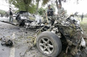 Police officers survey the site of a car bomb attack by suspected Muslim militants in Yala province, south of Bangkok July 17, 2009. Two soldiers